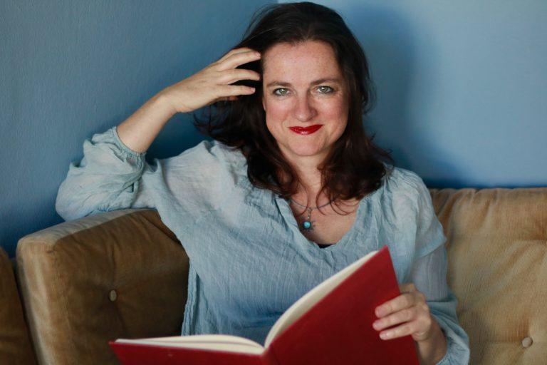 Daniela sitzt vor einer blauen Wand auf einem Sofa und hält ein Buch in der Hand