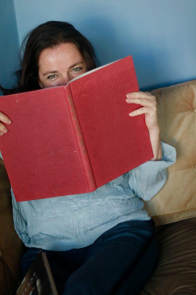 Daniela hält sich ein Buch vors Gesicht und lächelt über den oberen Rand hinweg.