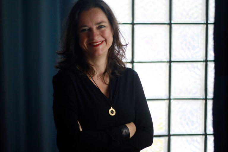 Daniela Tepper steht in einem dunklen Oberteil mit verschränkten Armen vor einer Glassteinwand.